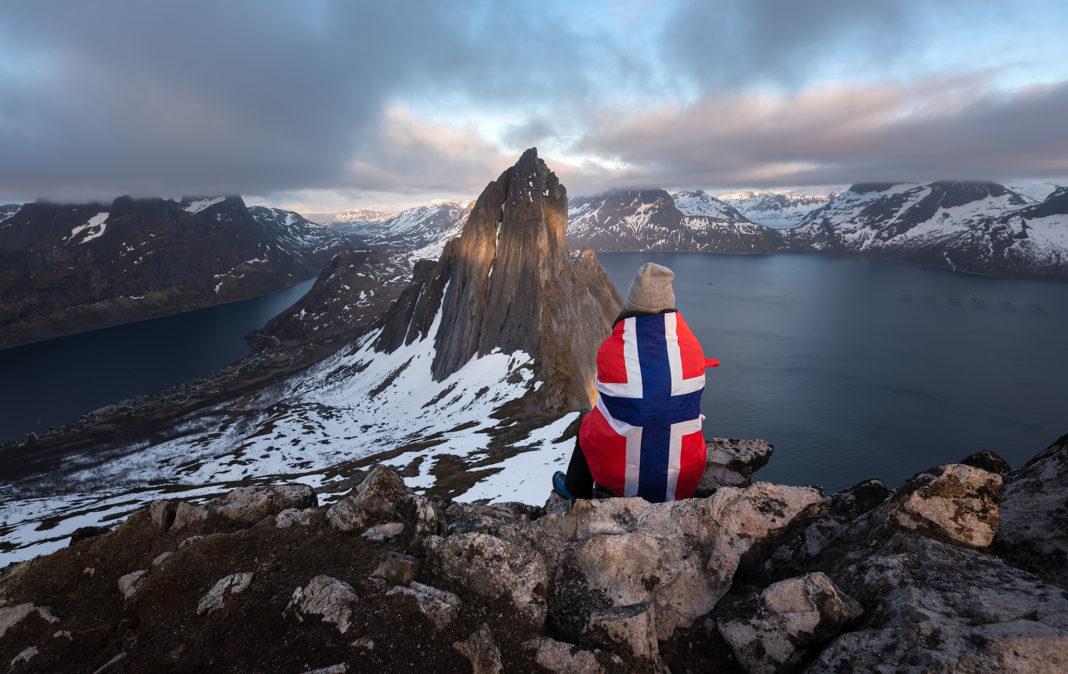Senja, Norwegia. Dziewczyna owinięta we flagę siedzi z widokiem na Segle. Szczyt Hesten